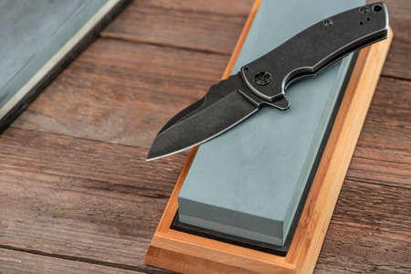 Steel pocket knife and whetstone on a rustic wooden background 免版税图像