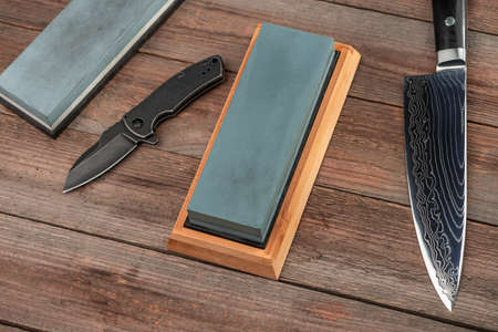 Top view on a jackknife, chefs knife and whetstones on rustic w