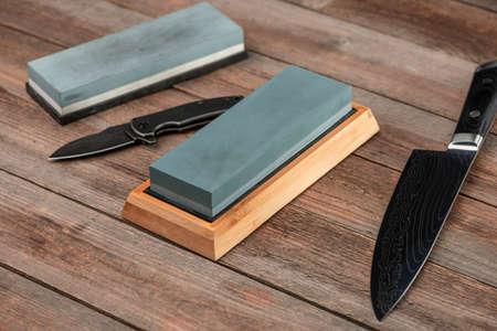 Whetstones, pocket knife and Japanese Gyuto knife on a wooden ta