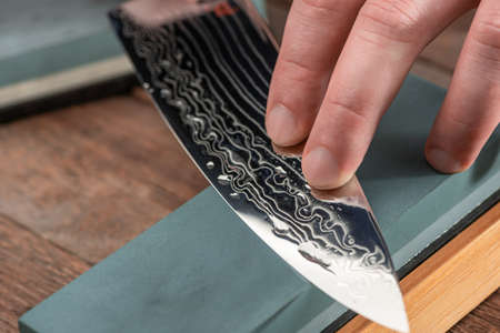 Close-up on a Damascus steel blade being sharpened with a whetst