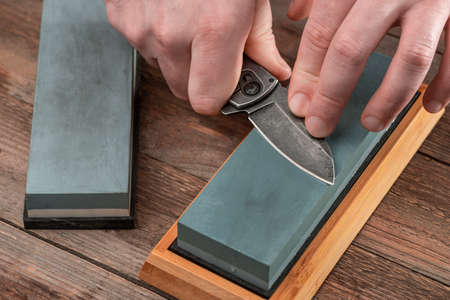 Man sharpening a jackknife with a whetstone on wooden background