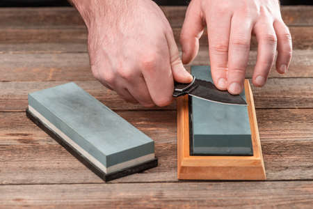 Mans hands sharpening a pocket knife with a whetstone on a wood