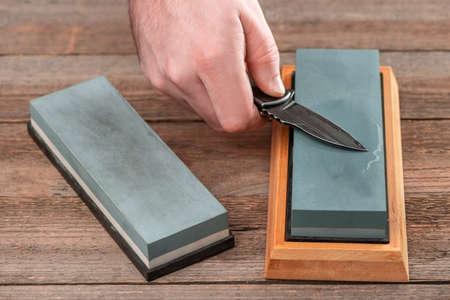 Man using a whetstone to sharp his pocket knife