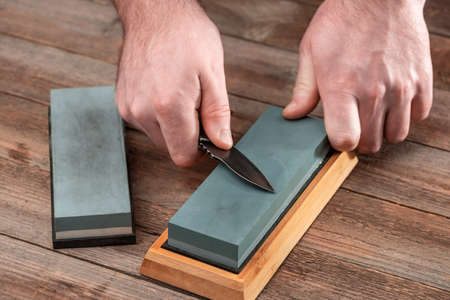 Man sharpening his jackknife with a whetstone on a rustic wooden
