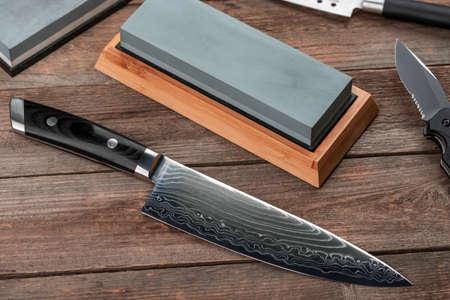 Top view on a Japanese Gyuto knife, a jackknife and a whetstone