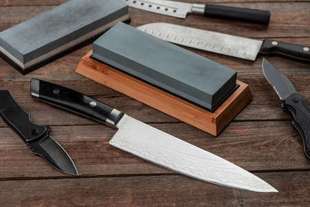 Assorted knives and whetstones on wooden table