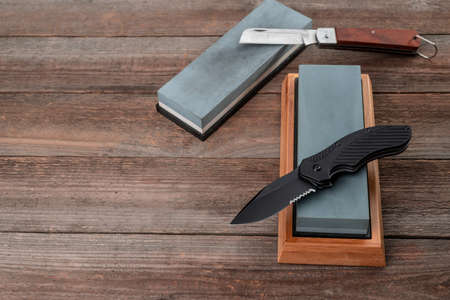 Different pocket knives and whetstones on rustic wooden backgrou