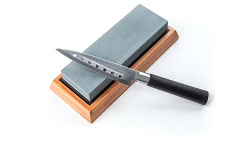 Cheese knife and a sharpening stone isolated on white background