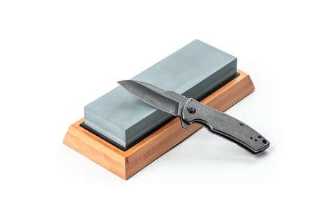 Black pocket knife and a whetstone isolated on white 免版税图像