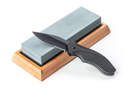 Folding pocket knife laying on a whetstone