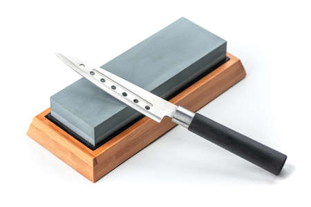 Cheese knife laying on a whetstone isolated on white background