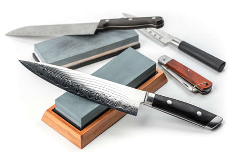 Assortment of various knives and whetstones on white background