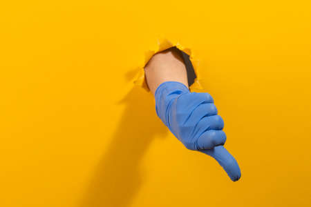 Hand in a latex glove showing a thumb down through torn yellow wall