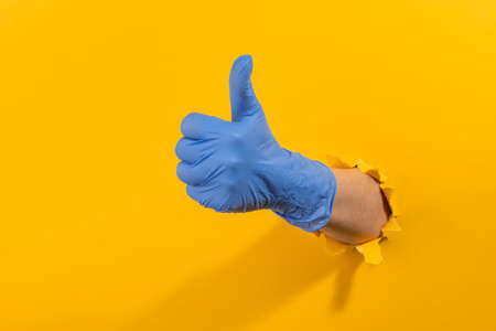 Hand in a latex glove showing a thumb up through torn yellow wall 写真素材