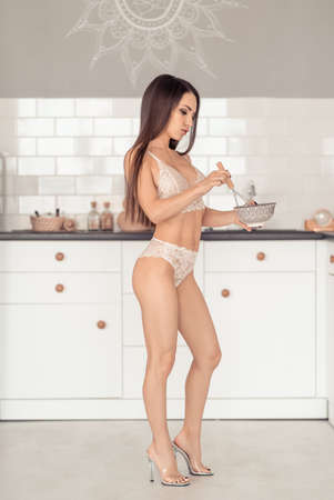 Young woman in white lingerie cooking at a kitchen Stock fotó