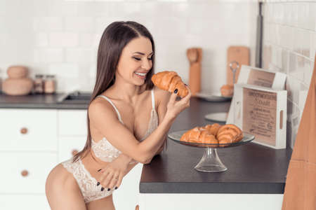 Young seductive woman in white lace underwear eating a fresh croissant Stock fotó