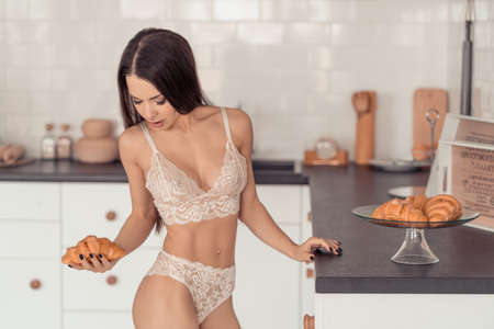 Young woman in lingerie came to kitchen for a croissant Stock fotó