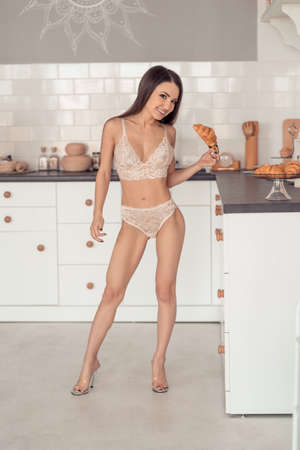 Beautiful adult woman in white underwear taking a croissant at kitchen