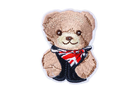 Teddy bear in blue jacket with UK neckerchief patch, isolated on white