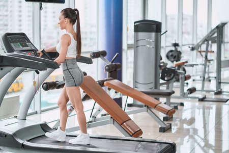 Fit woman walking on a treadmill in the gym