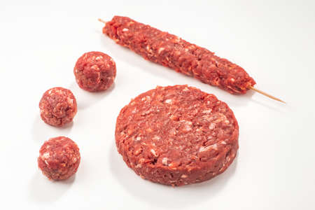 Close-up on raw meatballs, patty and kebab on white background