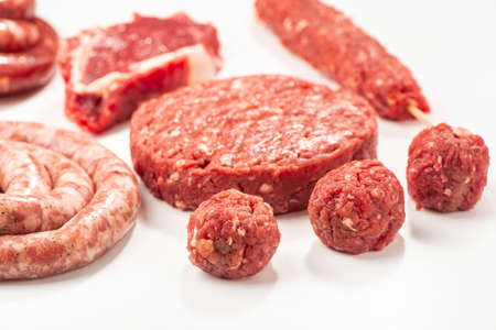 Close-up on raw meatballs, patty, sausage and kebab on white bac