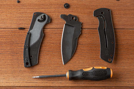 Top view on blade, handle of a disassembled knife and a screwdriver 免版税图像