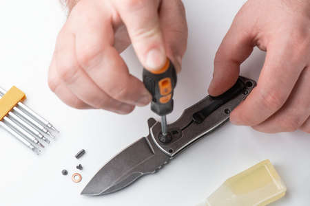 Technician joints the parts of a folding knife together with a screwdriver