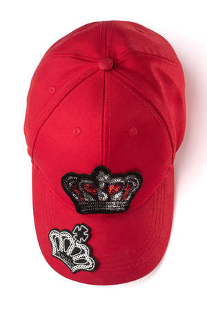 Red cap with sequin crown patches on white background