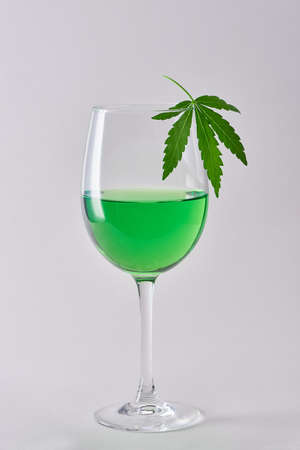 A glass of green hemp-infused wine on white background 写真素材