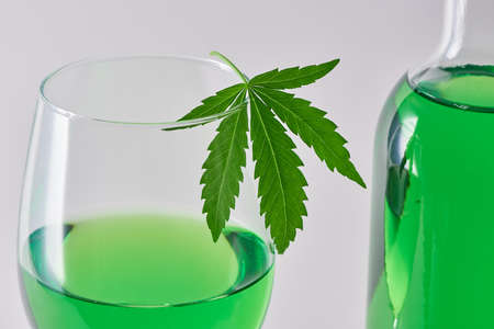 Close-up on a glass and a bottle of green weed wine on light background 写真素材