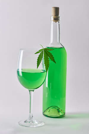 A glass and a bottle of green hemp-infused wine on white background