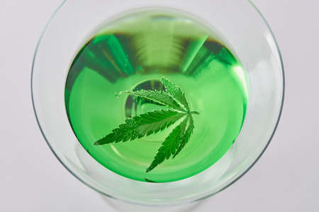 Close top view on a glass of a green cocktail with a cannabis leaf floating 写真素材