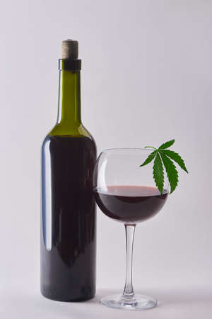 A bottle and a glass of cabernet with hemp infusion on white background 写真素材