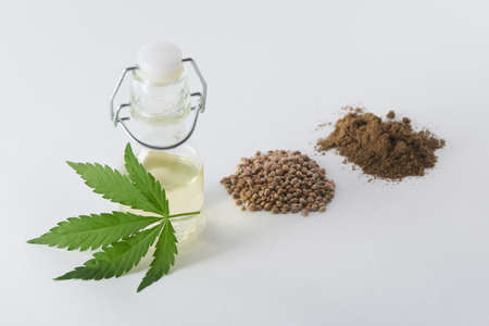 A leaf of hemp, a bottle of hempseed oil, seeds and a handful of flour on white 写真素材