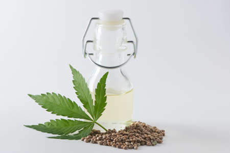 A bottle of hempseed oil with a hemp leaf and seeds on white background 写真素材