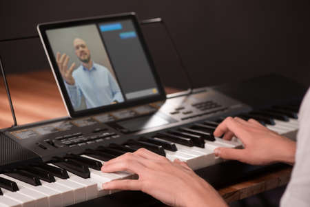 Young man learning to play piano, using keyboard and tablet with app