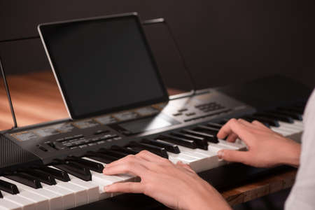 Young man learning to play piano, using keyboard and tablet with 写真素材