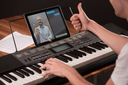 Student showing a thumb up to his music teacher during a piano lesson 写真素材