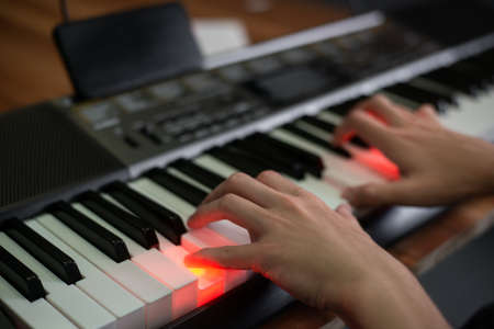 Man playing keyboard with lighting and looking at a display of a