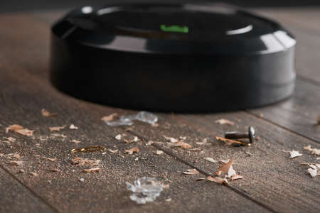 Close-up on dust and trash being collected by a black robotic va