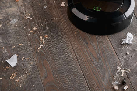 Black robotic vacuum cleaner leaving a clean trail on the dirty