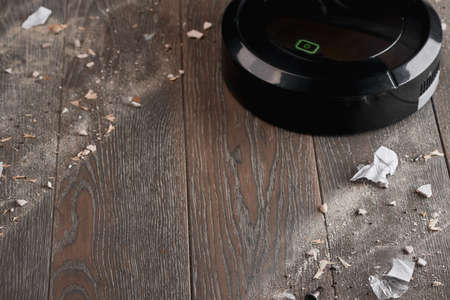 Black robotic vacuum cleaner cleaning wooden floor from trash