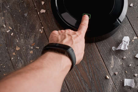 Man turning on a black robotic vacuum cleaner on dirty wooden fl