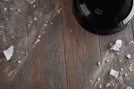 Top view on wooden floor being cleaned by a black robotic vacuum Reklamní fotografie