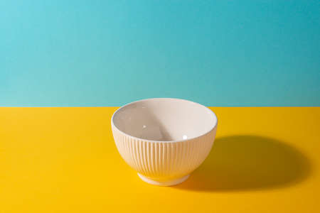 Empty ribbed beige bowl on bright background