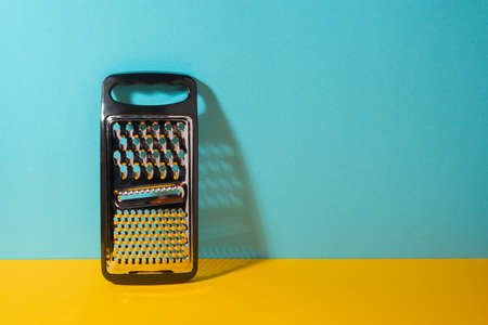 Stainless steel grater with plastic handle on yellow and blue background