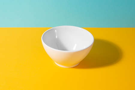 Empty white ceramic bowl on yellow and blue background Banque d'images