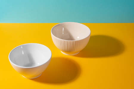 White and beige deep bowls on colorful background