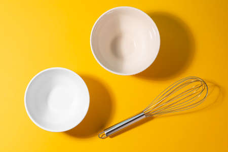 Top view on two different ceramic bowls and a metal whisk Banque d'images